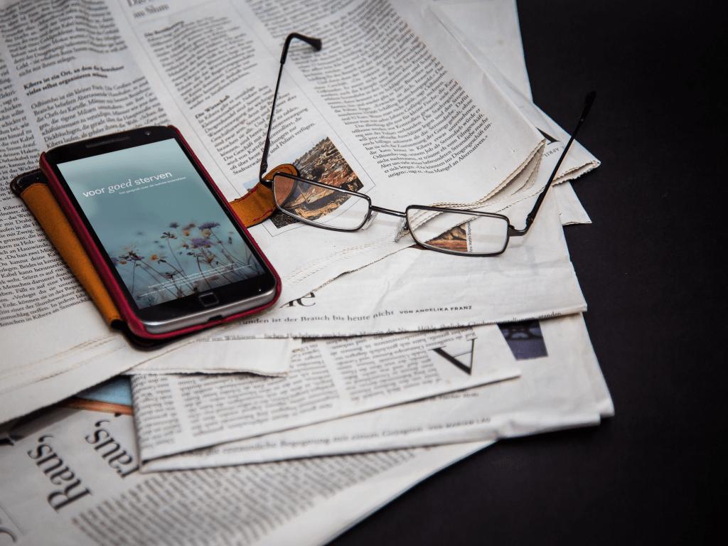 Telefoon met daarop de cover van Voor goed sterven, bovenop een krant.