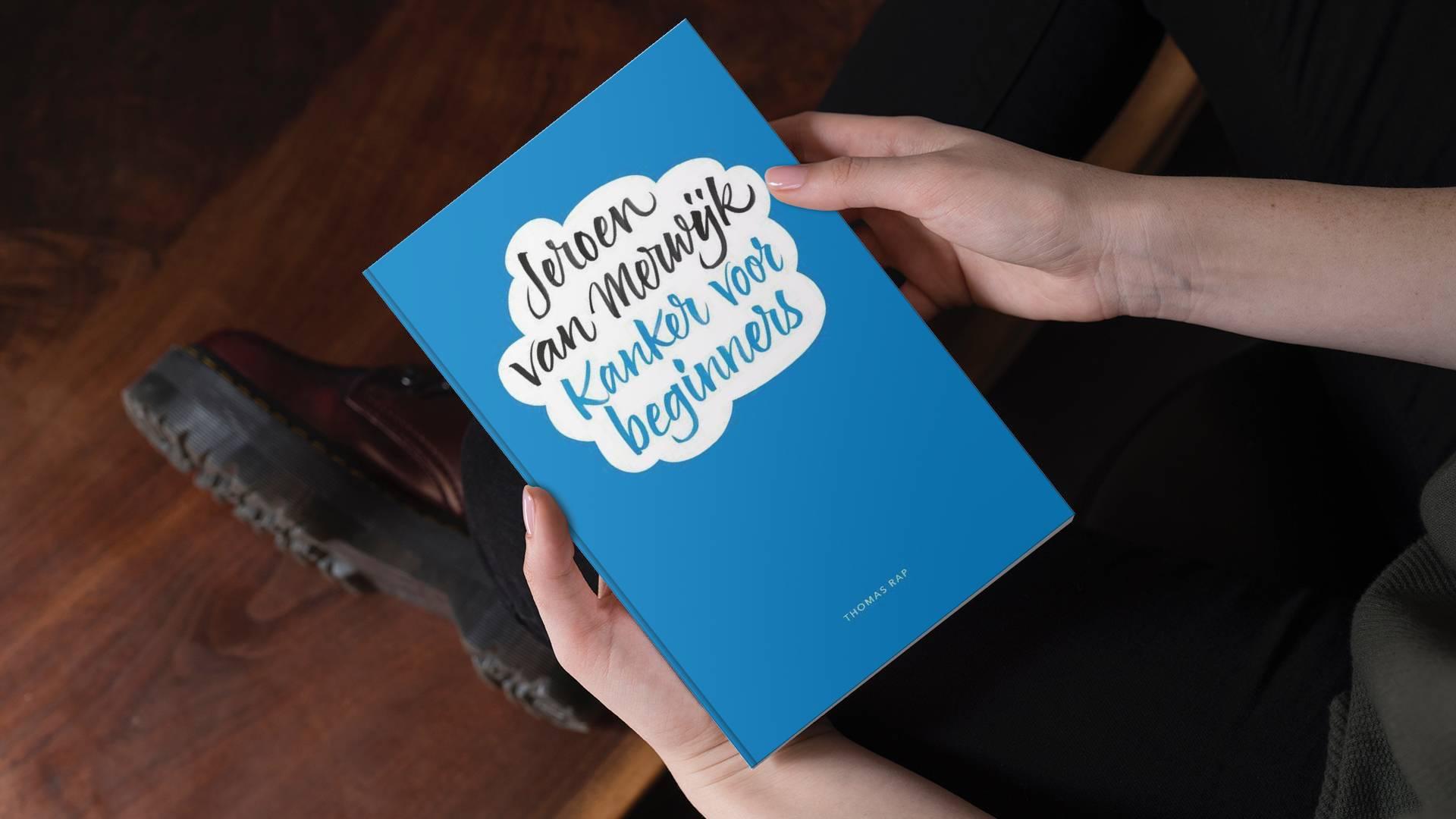 Boek 'Kanker voor beginners' door Jeroen van Merwijk in de handen van een man